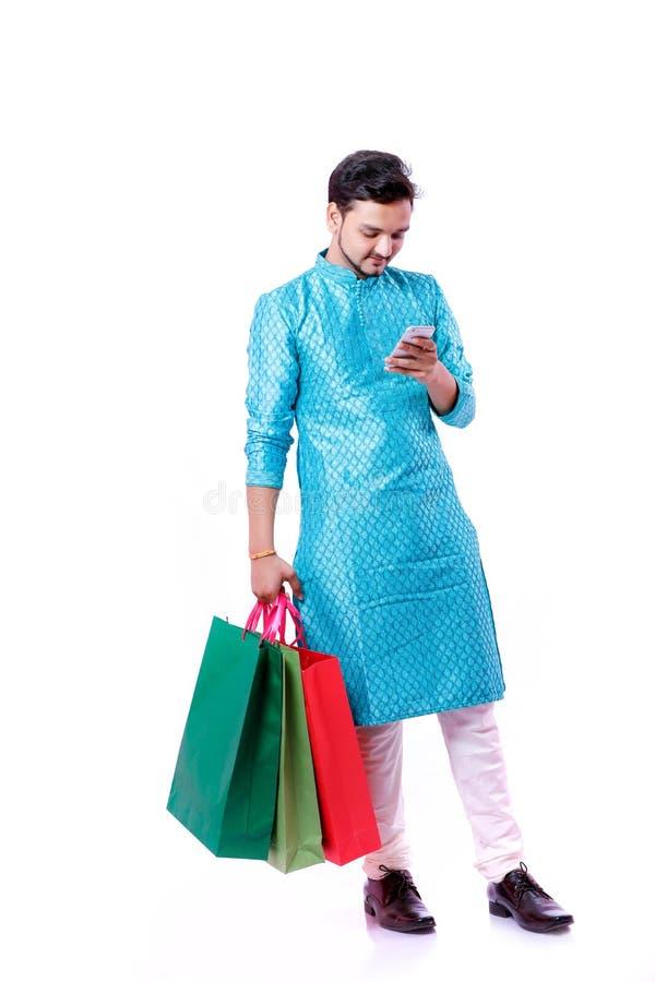 Индийский человек в этнической носке с хозяйственными сумками и показывать мобильный экран, изолированный над белой предпосылкой стоковое изображение rf