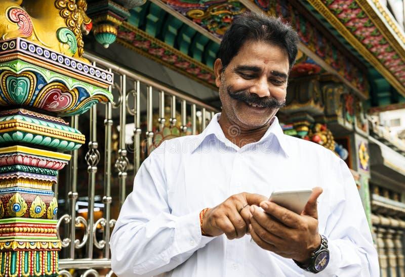 Индийский человек используя мобильный телефон стоковая фотография rf