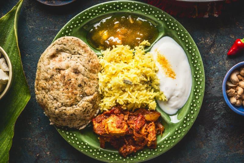 Индийский шар еды с карри, югуртом, рисом, хлебом, цыпленком, чатнями и специями стоковое изображение