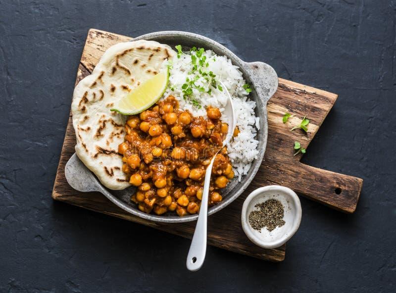 Индийское пряное карри нутов с рисом и naan хлебом в лотке на темной предпосылке, взгляде сверху стоковая фотография rf