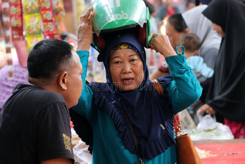 Индонезийская мусульманская домохозяйка нося вуаль и ходя по магазинам в рынке на гавани Muara Angke стоковые изображения