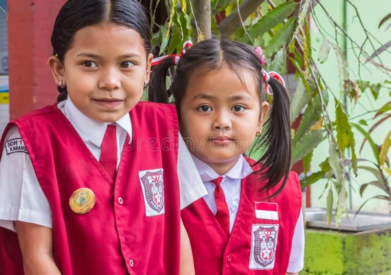 Индонезийские школьницы в форме представляя перед их школой стоковое изображение