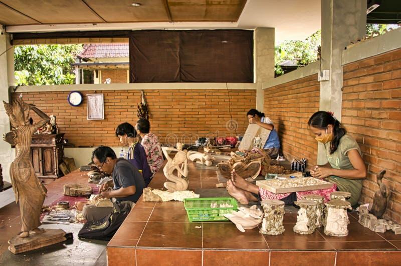 Индонезийский работник шкафа женщины и плотника людей работая с зубилом в его мастерской, сидя на поле Очень точный стоковая фотография rf