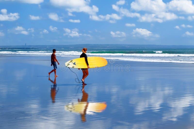 Индонезия, остров Бали, Kuta, пляж - 10-ое октября 2017: Серферы с surfboard идя вдоль пляжа стоковая фотография