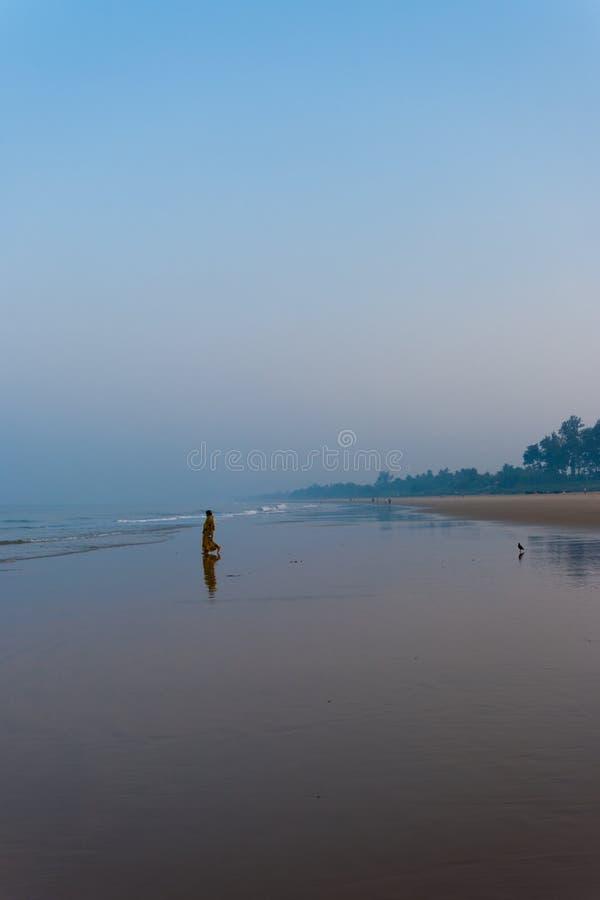 Индусский пляж женщины для того чтобы помолить утро Gokarna океана стоковые изображения rf