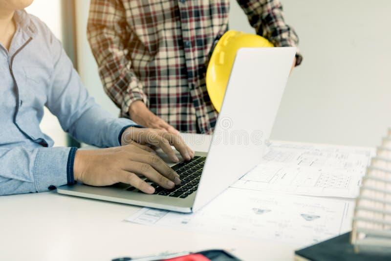 Инженерство обсуждая новый проект и используя ноутбук с colleag стоковые фото