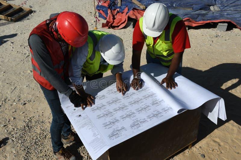 Инженеры в строительной площадке с светокопиями стоковое изображение