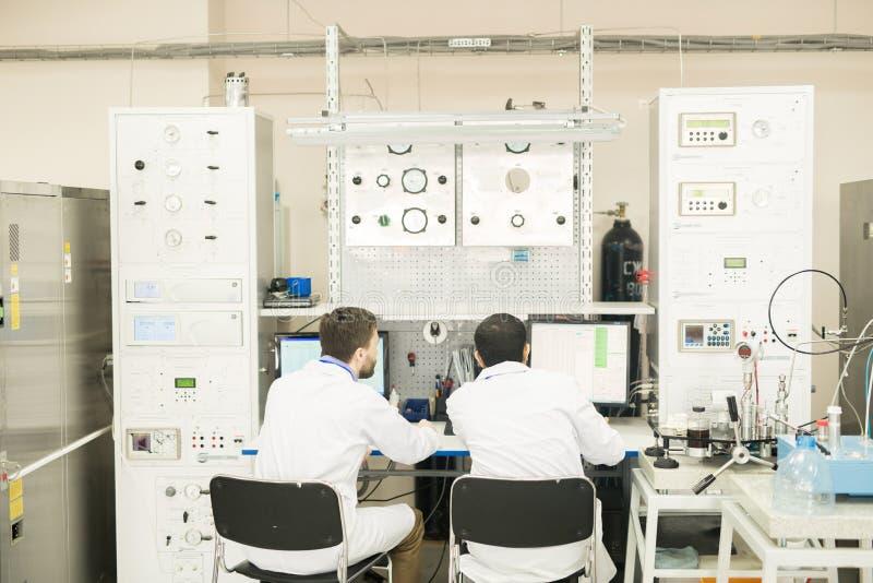 Инженеры работая с компьютером соединились к шкафу управления стоковое фото