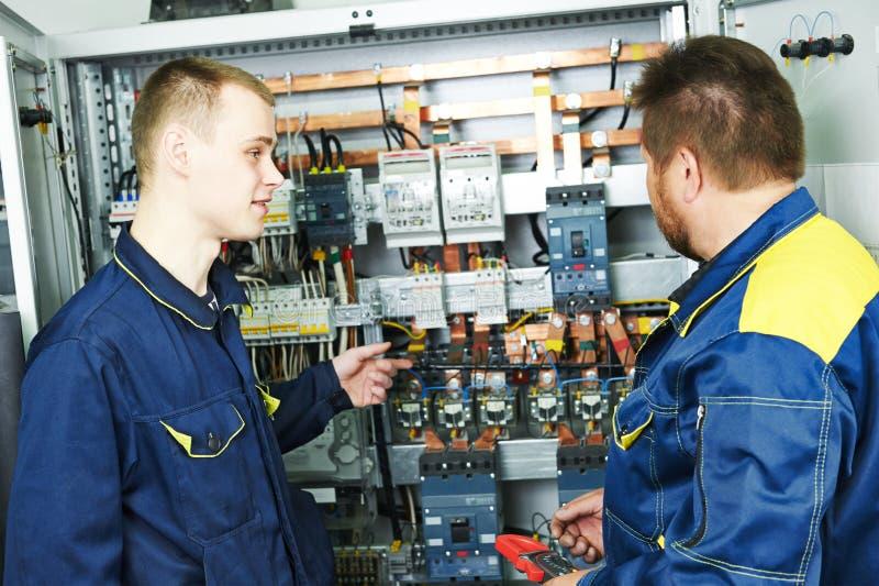 Инженеры электриков приближают к коробке распределения стоковые изображения