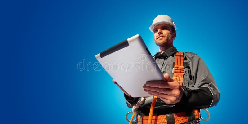 Инженер ветрянки строгая новый проект экологичности Он положение и взгляд в планшете Предпосылка студии цвета стоковая фотография rf