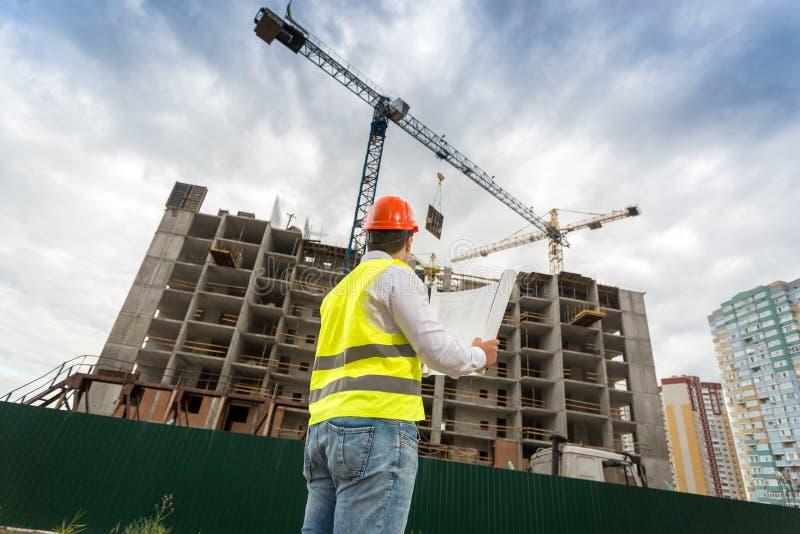 Инженер в защитном шлеме смотря здание под конструкцией стоковое изображение rf