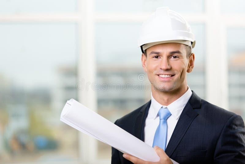Инженер в трудном шлеме вручает план стоковые изображения