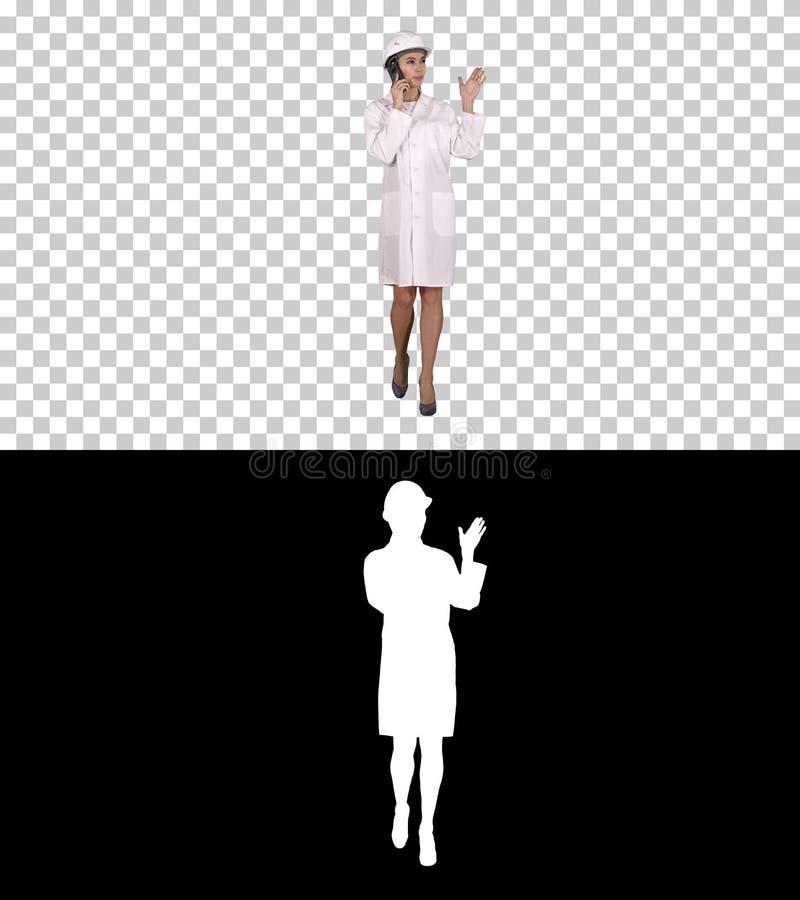 Инженер женщины говоря по телефону пока идущ, канал альфы стоковое изображение rf