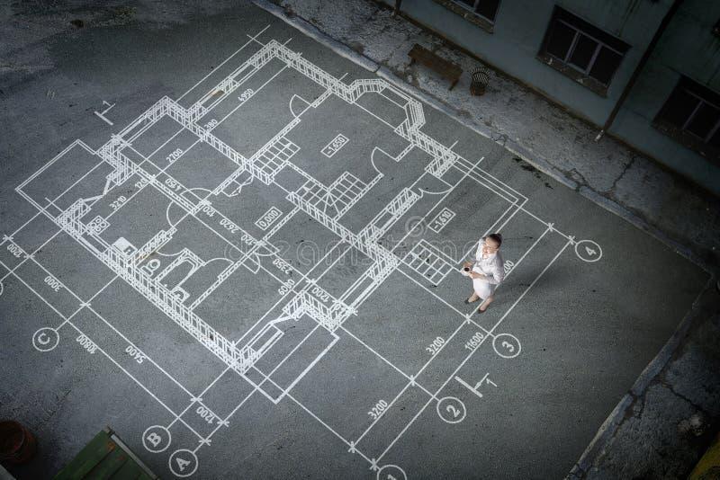 Инженер женщины думая над его планом Мультимедиа стоковое изображение