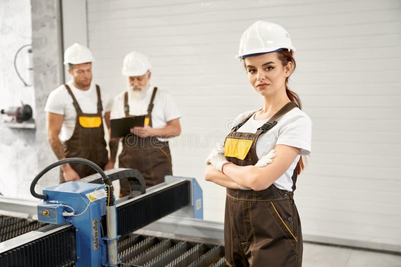 Инженер женщины представляя с работниками на фабрике механической обработки стоковая фотография rf