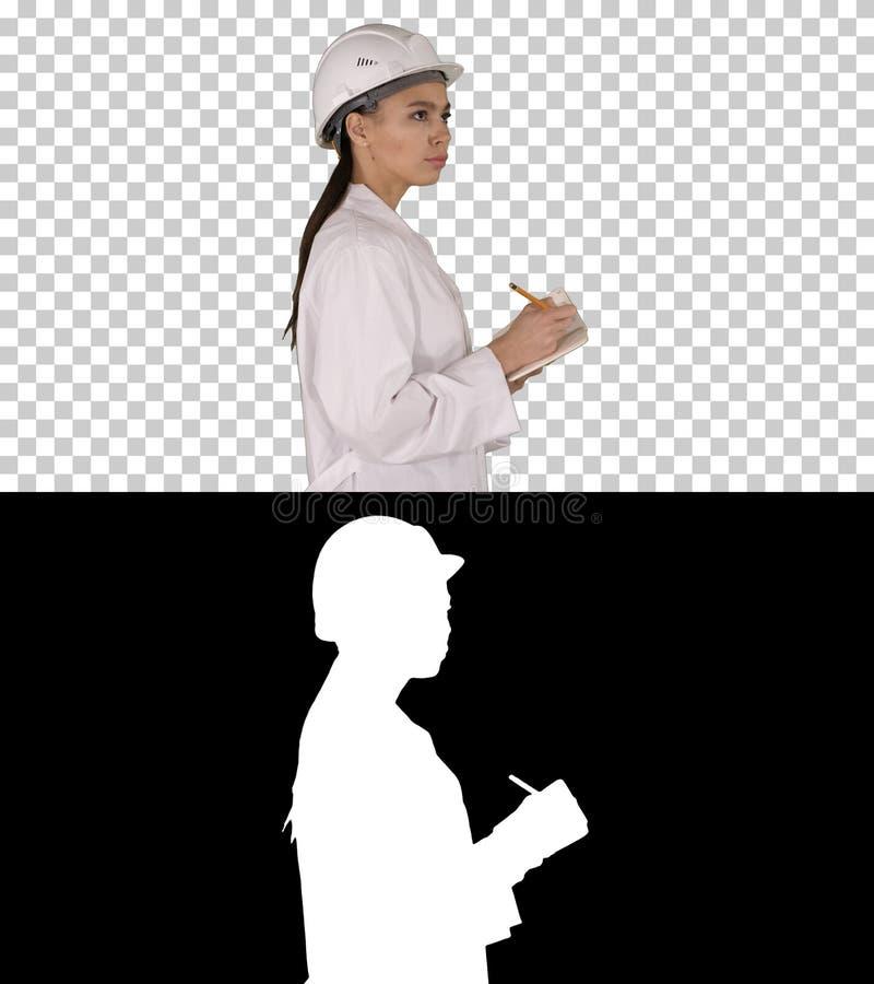 Инженер женщины со шлемом ручка и контрольный списоок удержания кладя что-то вниз пока идущ, канал альфы стоковая фотография