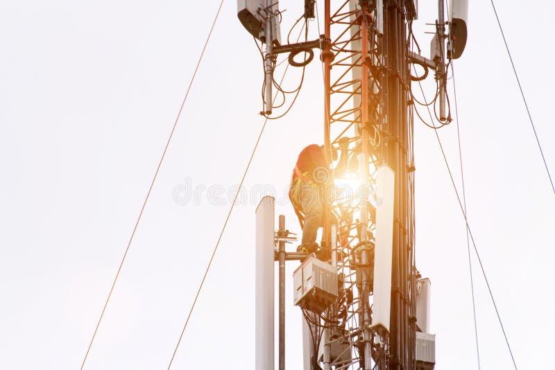 Инженер или техник работая на высокой башне, работе риска высокой работы, людей работают с оборудованием для обеспечения безопасн стоковая фотография