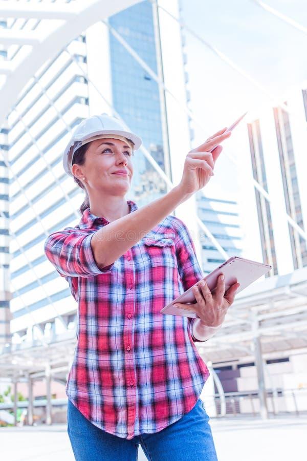 Инженер индустриального строительства носит инженерство шлема безопасности работая и используя цифровой планшет на снаружи здания стоковое изображение rf