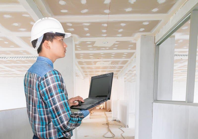 Инженер, использующий портативный компьютер, и надевающий пластик с белым шлемом в ходе осмотра конструкции внутри помещения стоковые изображения
