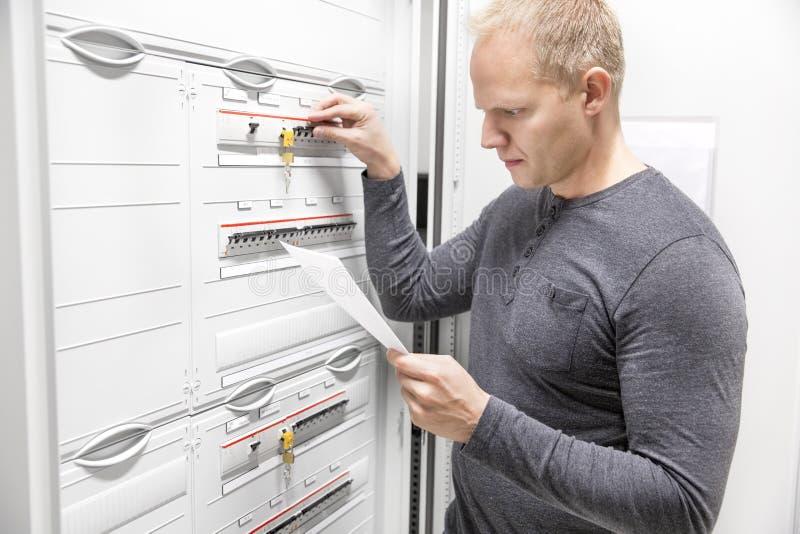 Инженер ИТ работает в большом шкафе взрывателя стоковое изображение
