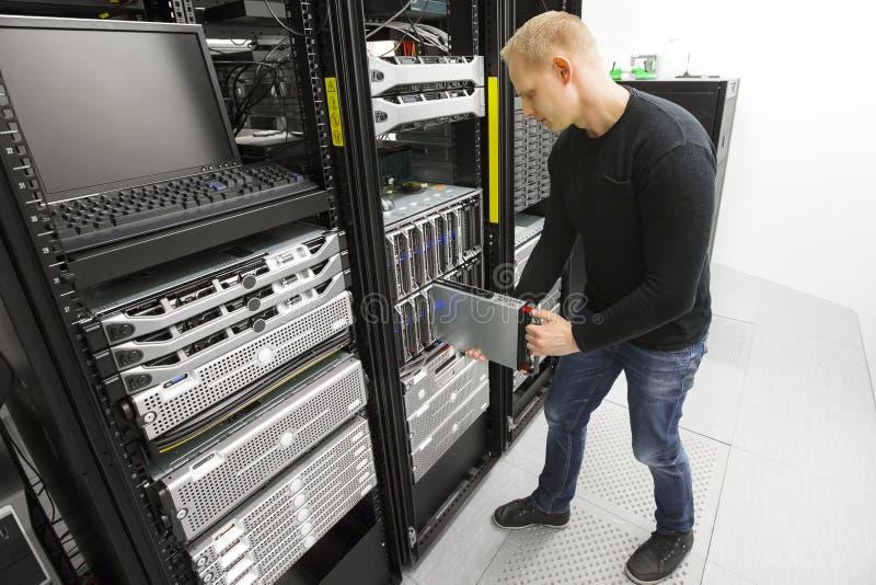 Инженер ИТ устанавливает сервера лезвия в datacenter стоковые фотографии rf
