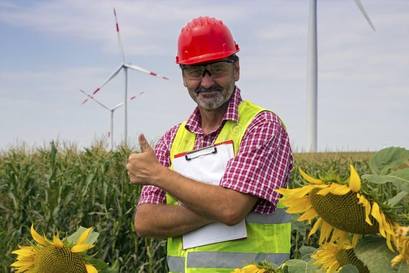 Инженер показывает большой палец руки вверх на парке энергии с ветротурбинами стоковая фотография rf