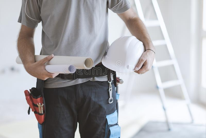 Инженер по строительству и монтажу держа шлем и проекты безопасности стоковое фото