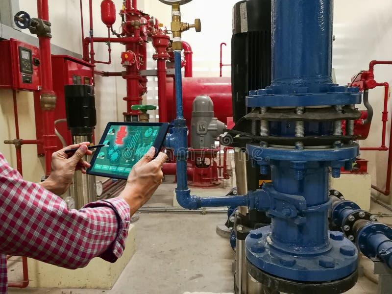 Инженер проверяет планшет системы индустрии прибора механический стоковая фотография