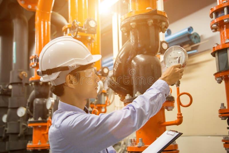 Инженер проверяя водяную помпу конденсатора и манометр, водяную помпу охладителя с манометром Готовое системы стоковое изображение