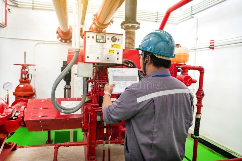 Инженер проверяя промышленную систему борьбы с пожарами генератора стоковые изображения rf