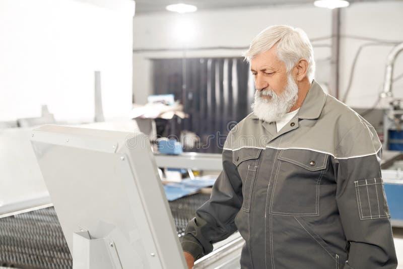 Инженер работая на фабрике с компьютеризированной машиной стоковая фотография rf