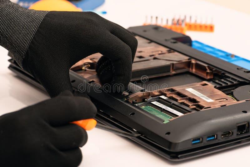 Инженер разбирает детали сломленного ноутбука для ремонта стоковые изображения rf