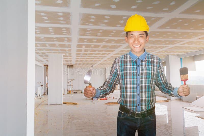 Инженер улыбается с ручной удерживающей троллейбурой и краской кистью износ желтой защитной шлемы пластика в строительстве стоковая фотография