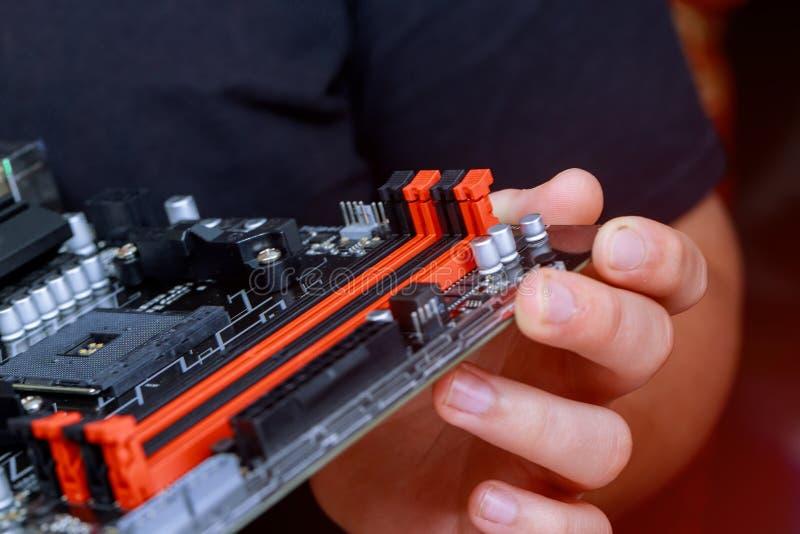Инженер устанавливая RAM памяти на компьютер материнской платы в лабораторию компьютера стоковые изображения rf