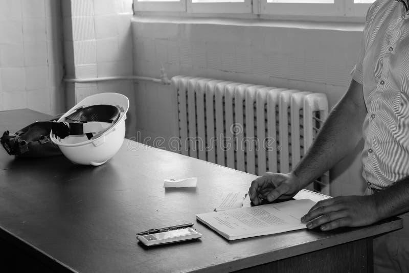 Инженер человека работая с белым шлемом на столе учит написать в тетради стоковые изображения