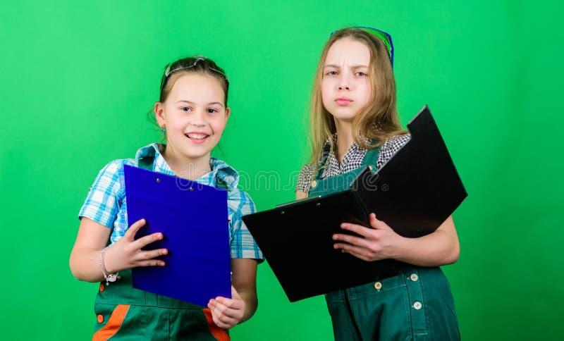 Инициативные девушки детей обеспечивают реновацию их предпосылка комнаты зеленая E План реновации Инженер построителя стоковая фотография rf