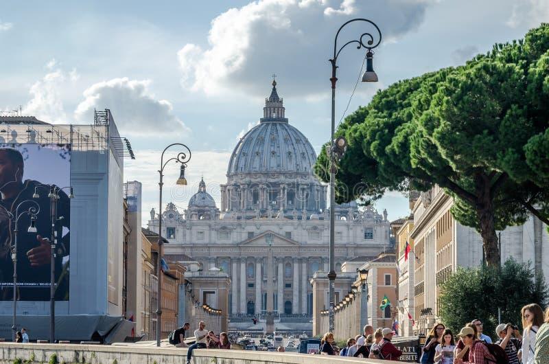 Иностранные туристы гуляя и будучи сфотографированными в Риме, Италии на яркий солнечный день перед куполом главного католика c стоковая фотография