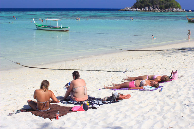 Иностранцы загорая на восходе солнца приставают к берегу на острове Lipe стоковое изображение rf