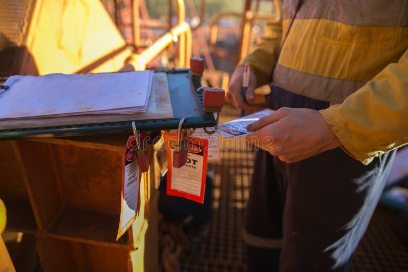 Инспектор горнорабочего проверяя имена на коробке замка разрешения изоляции для обеспечения получателей запирает в правильную кор стоковые изображения