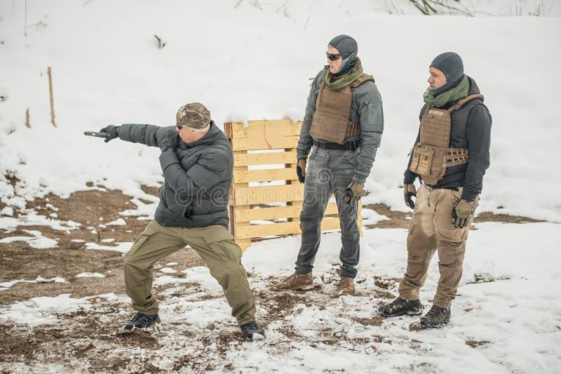 Инструктор демонстрирует стрельбу оружия боя действия тактическую к его студентам стоковая фотография
