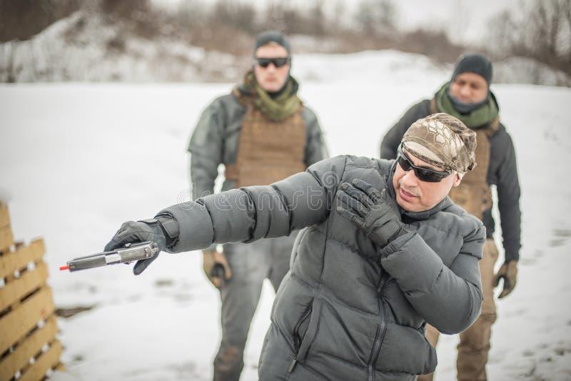 Инструктор демонстрирует стрельбу оружия боя действия тактическую к его студентам стоковое фото