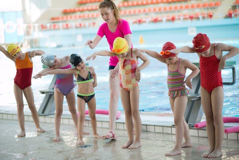 Инструктор и группа в составе дети делая тренировки около бассейна стоковые фото