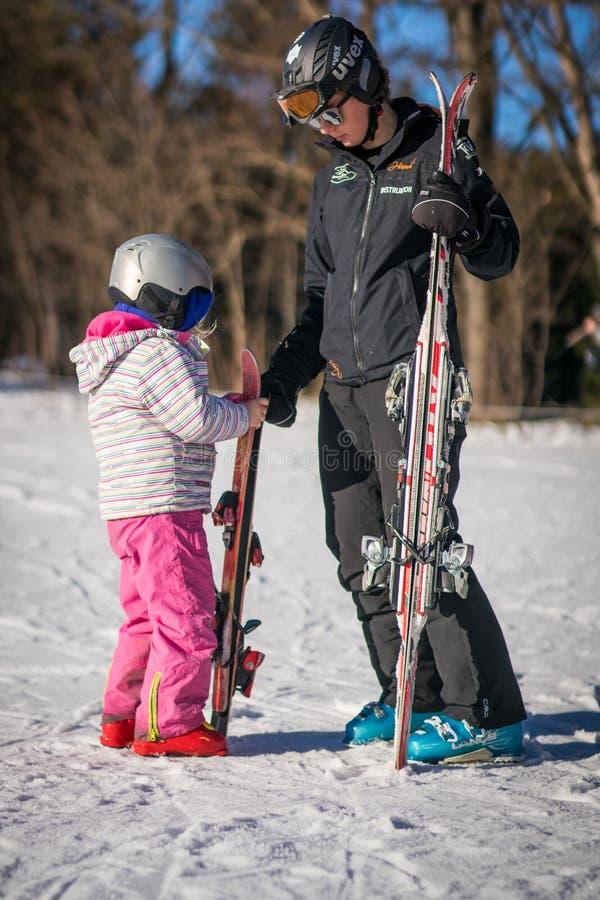 Инструктор и маленькая девочка лыжи стоковая фотография