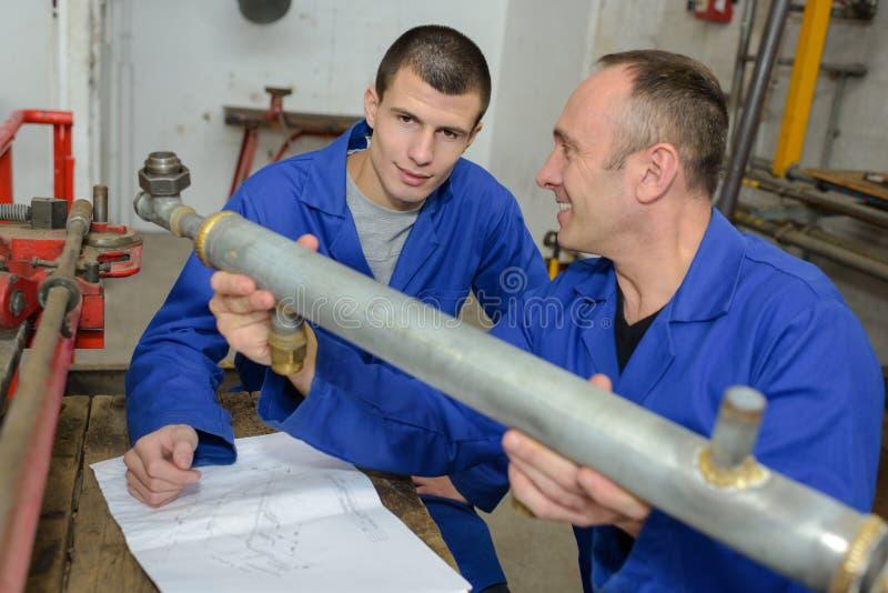Инструктор и подмастерье смотря трубу стоковые фотографии rf