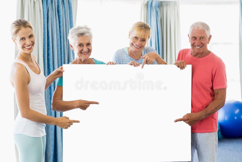 Инструктор и старшии держа плакат стоковое изображение