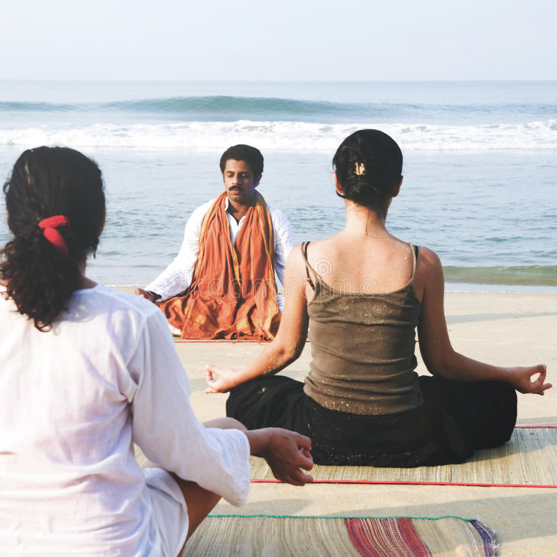 Инструктор йоги и его студенты концепцией пляжа стоковые изображения rf