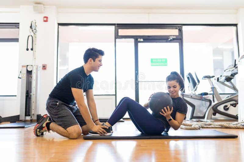 Инструктор помогая женщине в делать подбрюшную тренировку с Medi стоковые фотографии rf