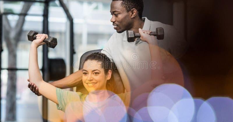 Инструктор помогая женщине в поднимаясь весах на спортзале стоковое фото