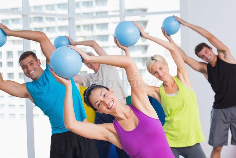 Инструктор при класс работая с шариками фитнеса стоковые изображения rf