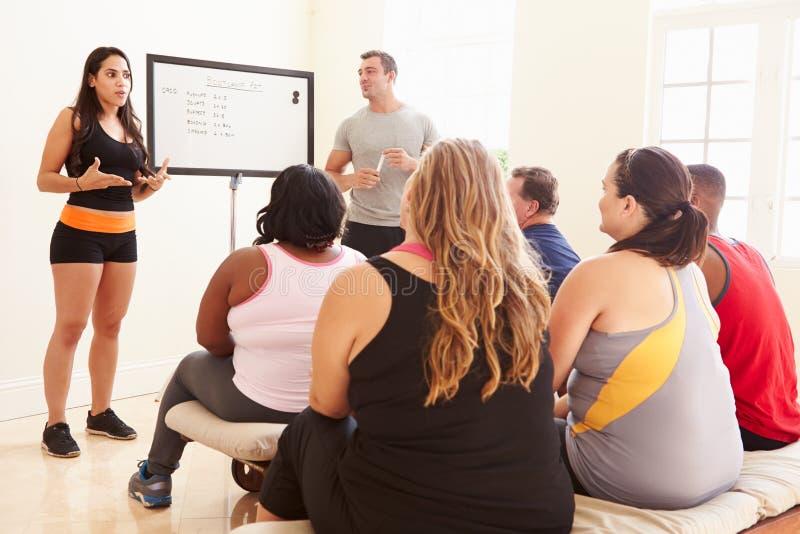 Инструктор фитнеса адресуя полные людей на клубе диеты стоковые фотографии rf